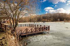 Wooden pier on lake covered by ice at sunny day Stock Photography