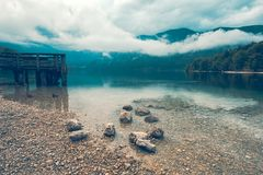 Wooden pier on the lake. Dramatic moody image with rainy clouds above the water surface. Image is taken on lake Bohinj in Slovenia Royalty Free Stock Photo