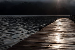 Wooden pier on the lake in the early morning. After rain. Sunrise.  Wet boards Royalty Free Stock Images