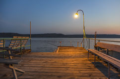 Wooden pier on the lake lit by lamp. Royalty Free Stock Photography
