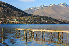 Wooden pier on lake with snowy background mountains Stock Photos