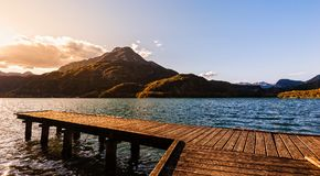 Wooden pier on the lake at sunset. Wooden pier on the lake at sunset with mountains in the background Royalty Free Stock Image