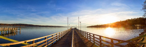 Wooden pier on the lake. And sunset - panorama in bavaria / germany Royalty Free Stock Image