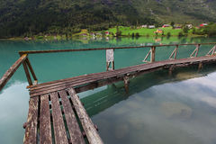 Wooden pier at the lake surrounded with villages Stock Photos
