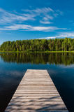Wooden pier on lake symmetrical scene Stock Photo