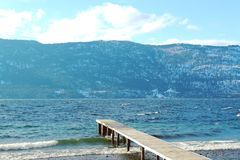 Wooden pier on lake in winter. With waves along shoreline of rocky beach. Mountains, lake and blue sky with clouds in background Stock Photos