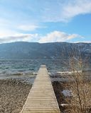 Wooden pier on lake in winter. With waves along shoreline of rocky beach. Mountains, lake and blue sky with clouds in background Royalty Free Stock Photos