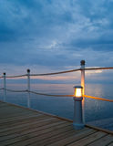 Wooden pier with lamp at sunset Stock Image