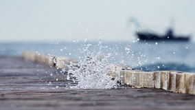 Wooden pier leading into the blue sea and the cascade of sea spr Stock Photos