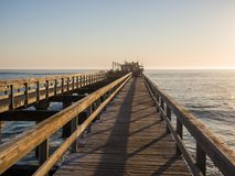 Wooden pier leading out into ocean with calm sea during soft sunset, Swakopmund, Namibia.  Stock Image