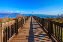 Wooden pier. Leading to the famous Lake Kinneret. Sunset on the Sea of Galilee Royalty Free Stock Photography