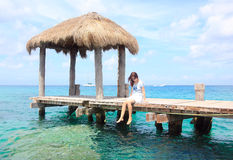 Wooden pier in mexico. A girl sitting on the bridge of a wooden pier in the caribbean Stock Photo