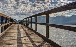 Wooden Pier in Mountainous Setting. An old wooden pier ventures out into Howe Sound in Squamish, B.C Royalty Free Stock Image