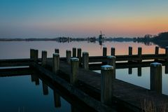 A wooden pier near a calm lake close to Rotterdam, Holland at sunset. royalty free stock image