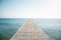 Wooden pier in the ocean with blue sky Stock Photography
