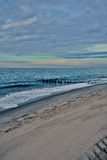Wooden Pier in Ocean at Sunrise Royalty Free Stock Photography