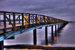 Wooden pier over sea. Scenic view of illuminated wooden pier over calm sea Royalty Free Stock Images