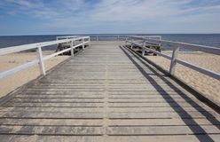 A wooden pier over the sea on lonely beach Stock Image