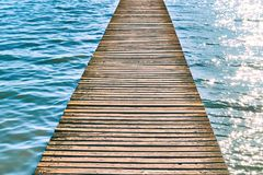 Wooden pier over water with waves on a sunny summer day royalty free stock images