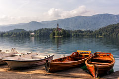 Wooden pier with pleasure boats on the water, lake Bled Royalty Free Stock Photo
