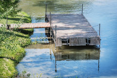 Wooden pier is reflected in the calm water Stock Images