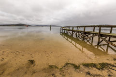 Wooden pier reflects Royalty Free Stock Image