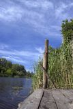 Wooden pier on river. Closeup of wooden fishing pier on river with blue sky and cloudscape background stock photography