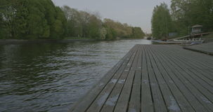 Wooden pier on the river in the evening in calm weather stock video