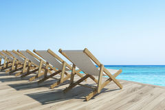 Wooden pier with a row of deck chairs Royalty Free Stock Image
