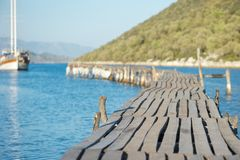 Wooden pier and sailing boat. An amazing picture of a wooden pier going into the sea with a boat coming towards it and beautiful green hills in background Stock Image
