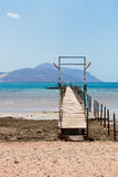 Wooden pier on the sandy beach of the Red Sea opposite the rocky Royalty Free Stock Image