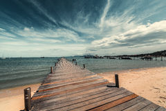 Wooden pier on the sandy shore. Stock Images