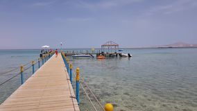 Wooden pier in the sea. Egypt, Sharm El Sheikh - May 06,2019 wooden pier in the sea. boats are moored at the pier, tourists are walking along the pier stock video