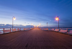 Wooden pier by the sea lit by stylish lamps at night. Gdynia Orlowo,Poland royalty free stock images