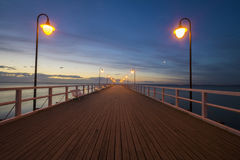 Wooden pier by the sea lit by stylish lamps at night Royalty Free Stock Image