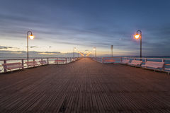 Wooden pier by the sea lit by stylish lamps at night. Gdynia Orlowo,Poland stock image