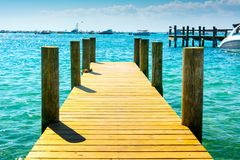 Wooden Pier in the Sea in a Sunny Day on Brlu Background. Destin Marina, Florida royalty free stock photography