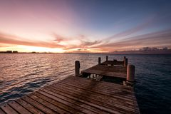 Wooden pier on the sea during sunset. Beautiful orange purple sk. Ies reflecting on the ocean. Grace Bay Beach, Providenciales, Turks and Caicos Stock Images
