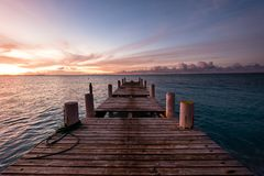 Wooden pier on the sea during sunset. Beautiful orange purple sk. Ies reflecting on the ocean. Grace Bay Beach, Providenciales, Turks and Caicos Stock Photos