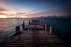 Wooden pier on the sea during sunset. Beautiful orange purple sk. Ies reflecting on the ocean. Grace Bay Beach, Providenciales, Turks and Caicos Stock Photography