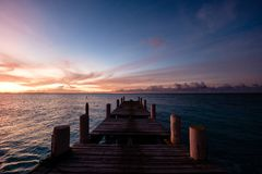 Wooden pier on the sea during sunset. Beautiful orange purple sk. Ies reflecting on the ocean. Grace Bay Beach, Providenciales, Turks and Caicos Royalty Free Stock Photography