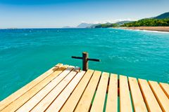 Wooden pier in the sea, the view of the mountains Stock Photos