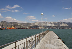 Wooden pier. At sea with the view of port and mountains and blue sky at the background, in Novorossiysk, Russian Federation stock photo
