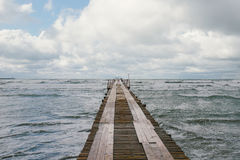 Wooden pier on the seashore with stormy sea Royalty Free Stock Image
