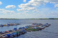 Wooden pier with small boats docked to it. Samara, Russia, Volga river stock images