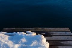 Wooden pier with snow on dark water background royalty free stock images
