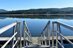 Wooden pier with stairs on a river with beach and forest. Water reflections, sunny day, blue sky. Galicia, Spain. royalty free stock image