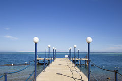 Wooden pier with street lights, fenced with iron ropes on the sh Stock Photography