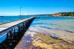 Wooden pier stretches out into clear bue water Stock Photo