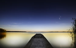 Wooden pier stretching out into colorful lake Stock Image